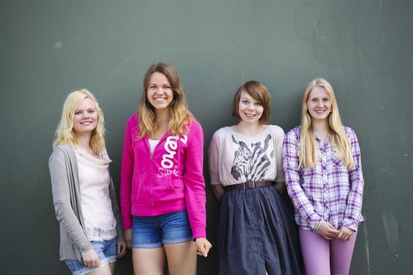 Kuvituskuva, nuoret naiset seisovat seinän edessä