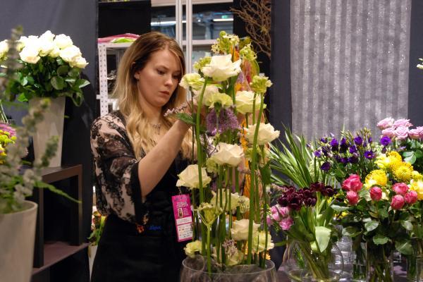 Kuvituskuva, floristi asettelee kukkia