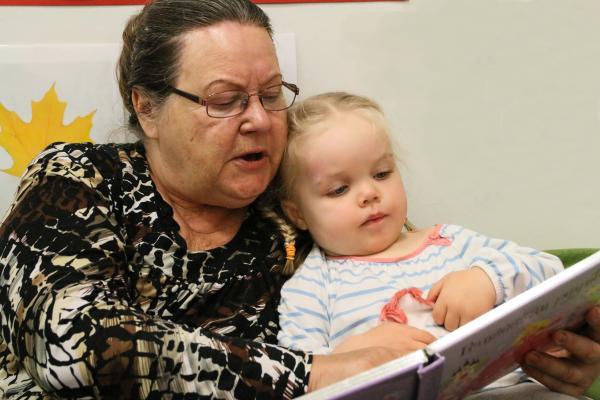 Kuvituskuva, lapsi on lukemassa aikuisen sylissä