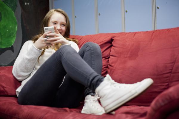 Kuvituskuva, tyttö makaa sohvalla kännykän kanssa
