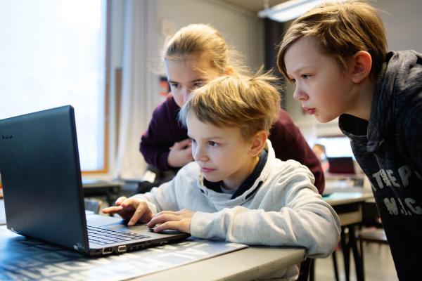 Kuvituskuva, kolme lasta tietokoneen ääressä