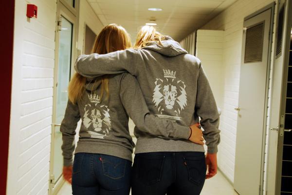 Girls embracing in a hallway