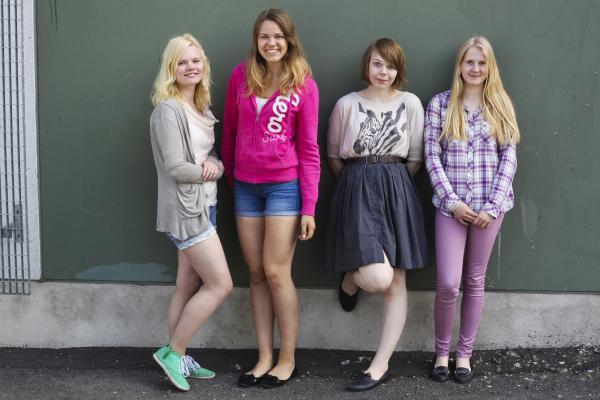 Nuoret naiset seisovat seinää vasten