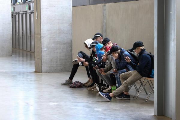 Joukko poikia katsoo kännyköitään rivissä