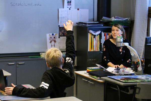 Nuori oppilas viittaa innokkaasti tunnilla