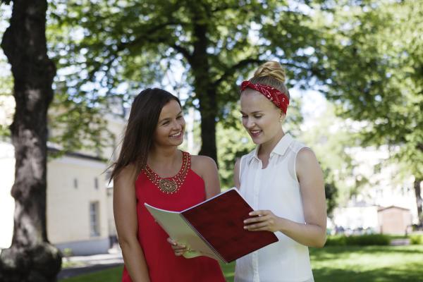 Kuvituskuva, kaksi opiskelijaa lukee kirjaa ulkona