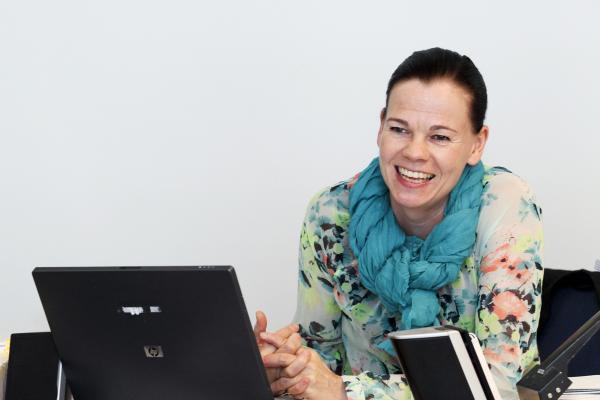 Kuvituskuva, opettaja hymyilee tietokoneen ääressä