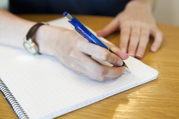 Kuvituskuva, nainen kirjoittaa muistiinpanoja muistivihkoon