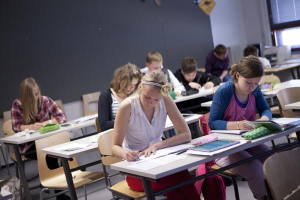Kuvituskuva, opiskelijat kirjoittamassa pulpetin ääressä