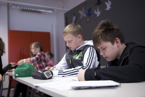 Kuvituskuva, pojat kirjoittavat pöydän ääressä