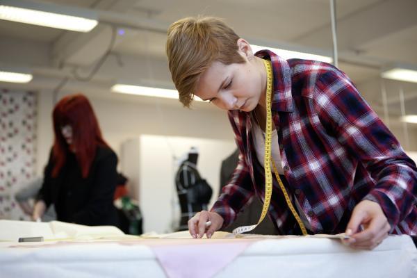 Kuvituskuva, opiskelija mittaa kangasta