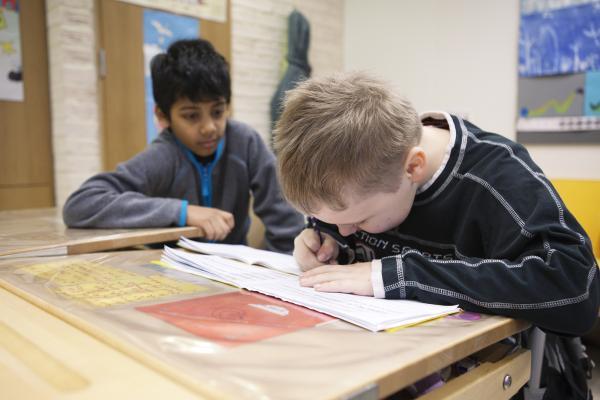 Kuvituskuva, poika kirjoittaa keskittyneesti