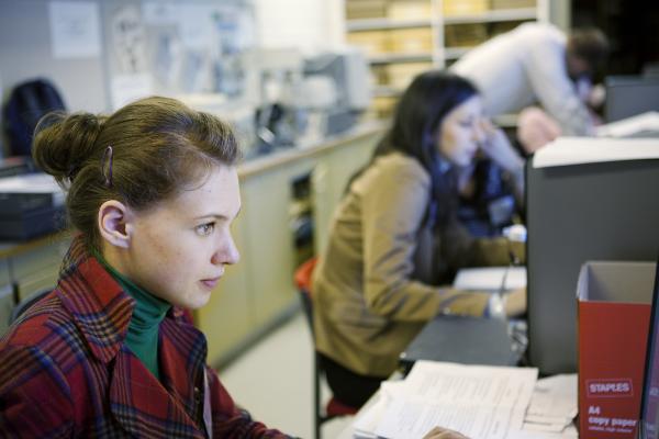 Kuvituskuva, nainen työskentelee tietokoneella
