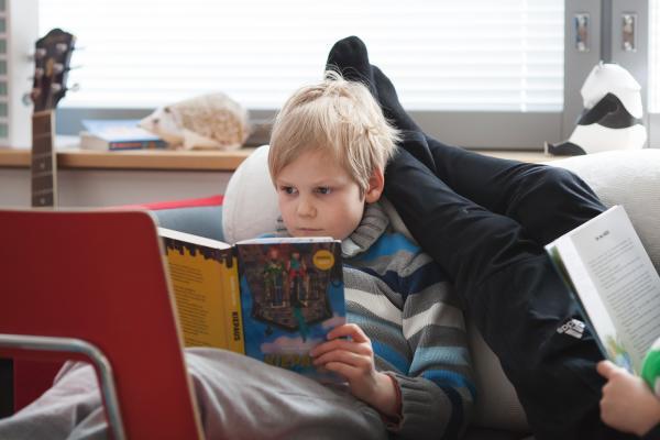 Kuvituskuva, lapsi lukee kirjaa
