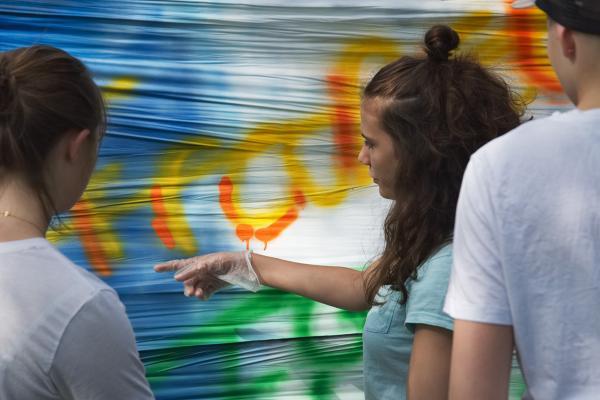 Kuvituskuva: Nuoret maalaavat lakanaa spray-maalilla