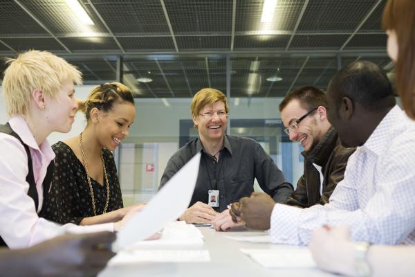 Kuvituskuva: osallistujat nauravat kokouksessa