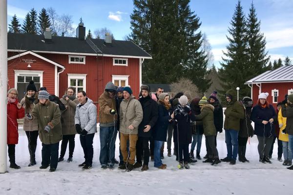 Ryhmä nuorisotyöntekijöitä seisoo rivissä ulkona talvella