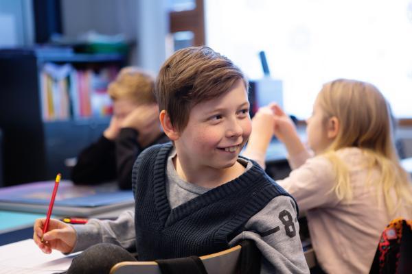 Kuvituskuva: hymyilevä poika kääntyneenä tuolillaan taaksepäin