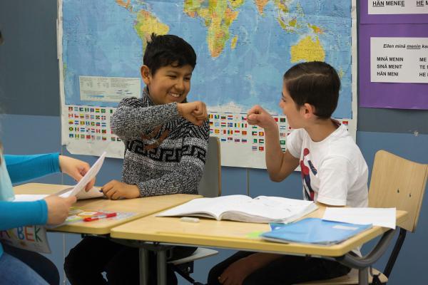 Kuvituskuva: pojat lyövät nyrkit yhteen yhteistyön merkiksi