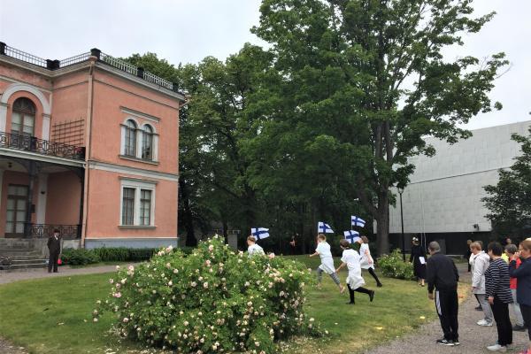 Neljä ihmistä juoksemassa Suomen liput kädessä Hakasalmen huvilan edustalla. Juoksevien ihmisten takana noin kahdeksan ihmistä odottavat vuoroaan.
