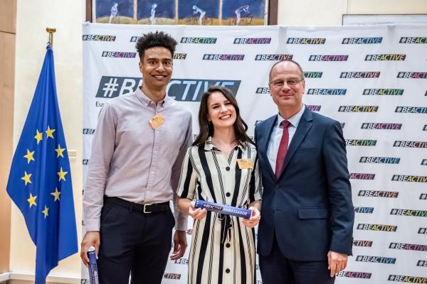 #BeActive Euroopan urheiluviikon kansalliset lähettiläät Shawn Huff ja naisten cheermaajoukkuetta edustava Rosanna Toivonen poseeraavat diplomien jaon yhteydessä komissaari Tibor Navracsicsin kanssa Euroopan komissiossa