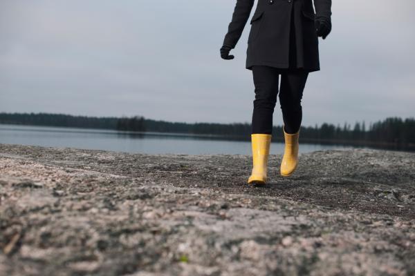 Henkilö kävelee kalliolla keltaisissa kumisaappaissa