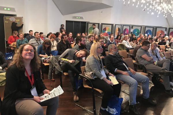 Kuvassa on sali, jossa istuu satakunta ihmistä kuuntelemassa puhujaa.