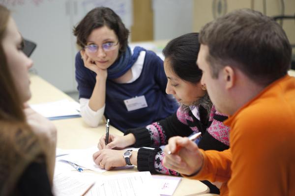 Aikuisia opiskelijoita pöydän ääressä