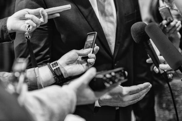 Mieshenkilöä haastatellaan erilaisin mikrofonein ja sanelimin