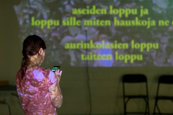 Nainen videokankaan edessä teoksessa The End Anti-festivaalilla Kuopiossa
