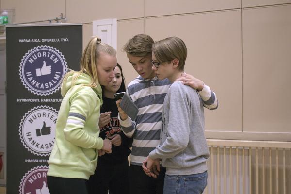 Neljä nuorta tutkii puhelinta