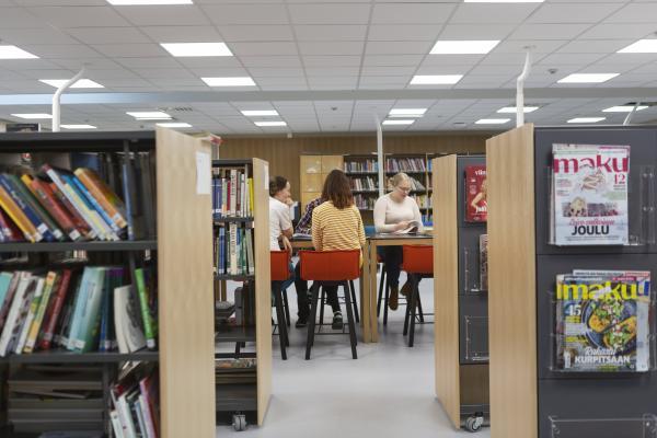 Näkymä oppilaitoksen kirjastoon ja taustalla opiskelijaryhmä työskentelemässä