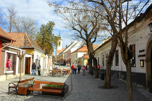 Näkymä vanhan kaupungin mukulakivikadulle, ihmisiä ja kahvilaterassi