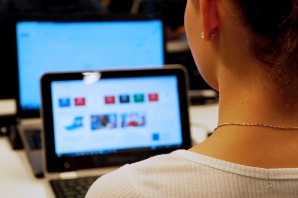 Selin oleva tyttö istuu tietokoneen ääressä