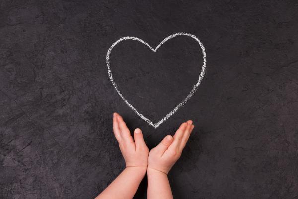 Lapsen kädet ja liitutauluun piirretty sydän.