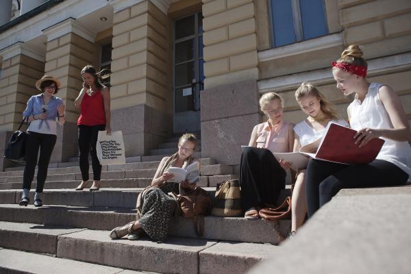 Tyttöjä istuu opiskelemassa yliopistorakennuksen portailla kesällä.
