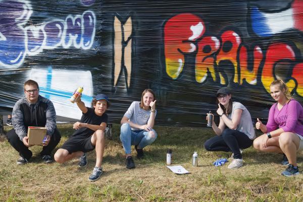 Kansainvälisen nuorisotapaamisen nuoria graffitia maalaamassa