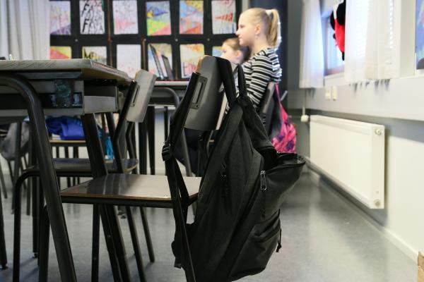 Reppu roikkuu pulpetin tuolin selkänojasta, taustalla oppilaita.