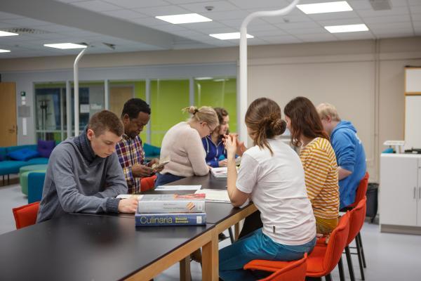 Ryhmä ammatillisen koulutuksen opiskelijoita työskentelee korkean pöydän ääressä
