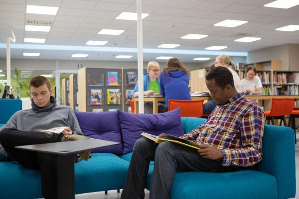 Kaksi miestä opiskelijakirjaston sohvalla lukemassa. Taustalla muita pöydän ääressä.