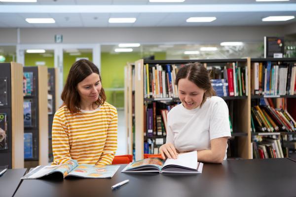 Kaksi naisopiskelijaa pöydän ääressä ammatillisen oppilaitoksen opiskelijakirjastossa.