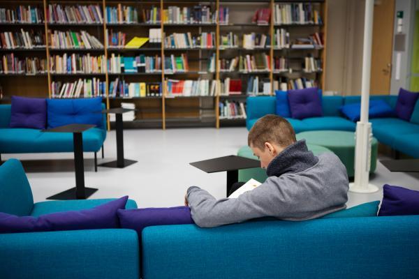 Mies sohvalla ammatillisen oppilaitoksen opiskelijakirjastossa selin kameraan