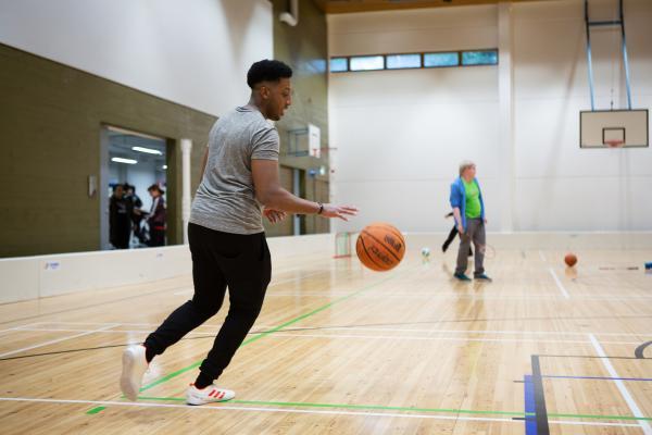 Miesopiskelija pompottaa koripalloa liikuntasalissa. Taustalla muita opiskelijoita.