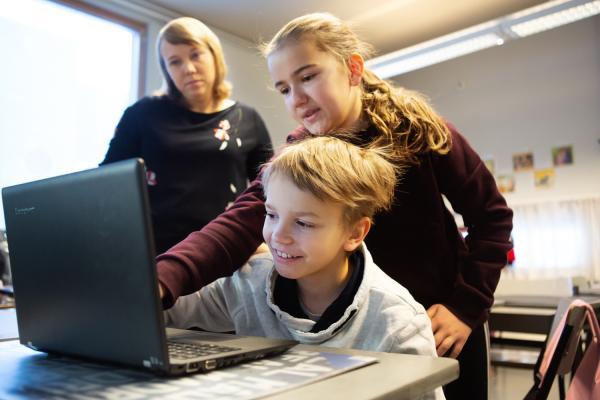 En pojke och en flicka studerar vid datorn. I bakgrunden ser läraren på.
