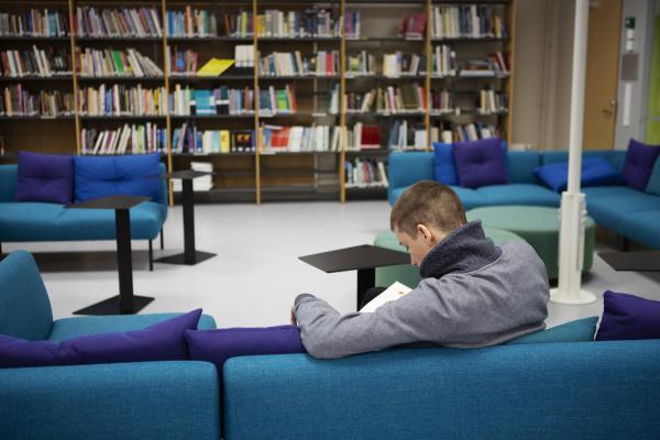 Kuvituskuvassa nuori mies lukee kirjastossa