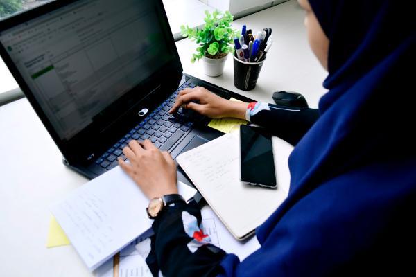 Musliminainen opiskelee kannettavan tietokoneen ääressä.