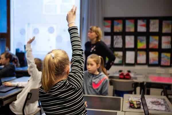 Oppilas viittaa luokassa.