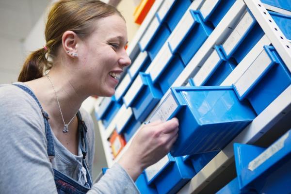 Kuvituskuva, jossa nainen avaa työkalulaatikoston lokeroa