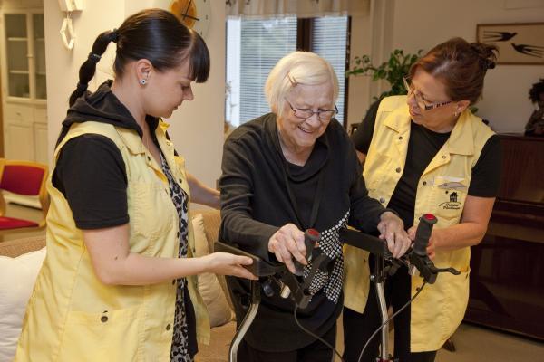Kuvituskuvassa hoitajat auttavat vanhusta liikkumaan