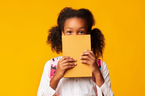 Tyttö pitelee kirjaa kasvojensa edessä